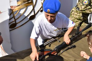 A boy disassembling and assembling a Kalashnikov on Red Square, Moscow.